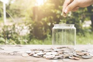 Mano poniendo monedas de dinero en un tarro de cristal foto