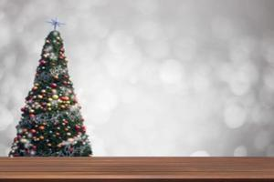 Wood table on soft blur Christmas tree background photo