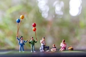 Miniature figurines of a family sitting in a park