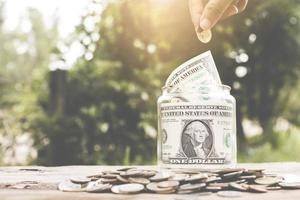 concepto de ahorro de dinero, mano poniendo dinero en frasco de vidrio foto