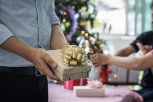 Hombre sujetando una caja de regalo para regalar en navidad foto