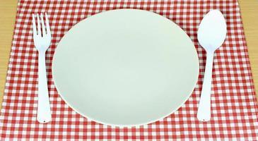 plato blanco y cubiertos sobre tela foto