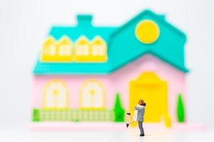 Two miniature figurine people hugging in front of a house