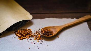 Red chili flakes on wooden spoon