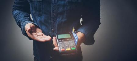 persona sosteniendo una máquina de tarjetas de crédito foto