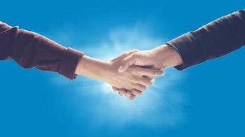 Business handshake against blue background photo