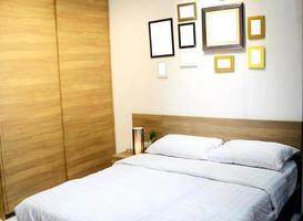 dormitorio con marcos de cuadros en blanco