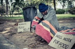 Homeless man with cardboard sign photo