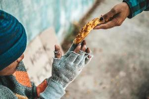 The bread-maker gives to a beggar on the side of the road photo