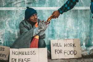 The bread-makers give to a beggar on the side of the road photo