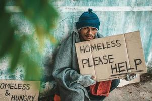 Person gives to a beggar on the side of the road photo