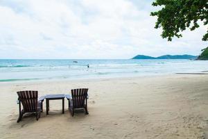 sillas y mesa en la playa foto