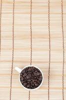 granos de cafe en una taza blanca