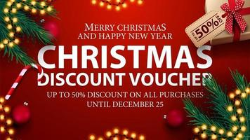 Christmas discount voucher, up to 50 off on all purchases. Red discount voucher with presents, Christmas tree branches, candy canes and Christmas balls vector