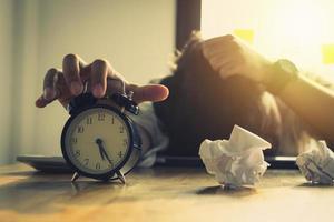 Persona de negocios sentada frente al reloj despertador con papeles arrugados foto