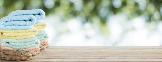 Toallas en canasta sobre mesa de madera foto