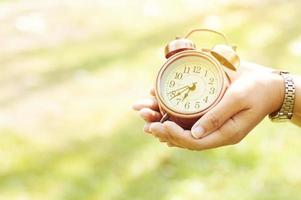 Alarm clock in hand on natural background