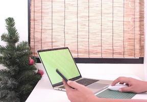 Persona que trabaja en la computadora portátil con el árbol de Navidad en la maqueta de la oficina foto