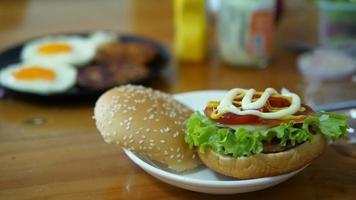 senhora fazendo hambúrguer com ovos borrados no fundo da mesa de madeira