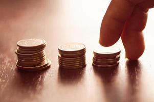dedos intensificando pilas de monedas