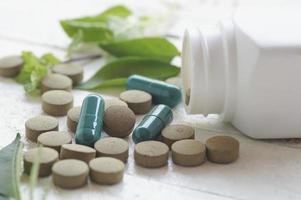 cápsulas verdes y pastillas de color marrón foto