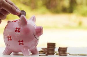 Putting money into a piggy bank photo