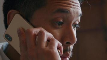asiatisk ung man ringer fokuserad med mobiltelefon video