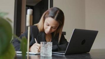 jovem empresária negra sentada à mesa com videochamada, conversando, ouvindo e fazendo anotações video