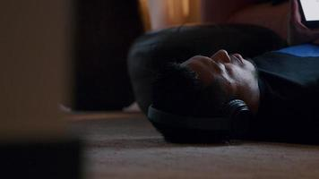 cabeça de um jovem asiático, deitado no tapete, fone de ouvido, assistindo o tablet na frente dele video