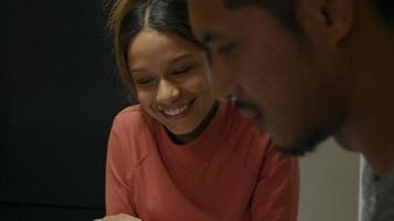 mujer joven negra y joven asiático viendo tablet - no se muestra el dispositivo