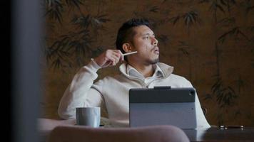 jovem asiático com laptop e caneta olhando contemplativamente video