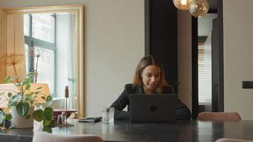 jovem empresária negra sentada à mesa com videochamada, falando constantemente video