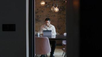 Asian young man sitting at table with laptop, having conversation by video call on laptop