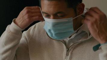 asiatischer junger Mann setzt Gesichtsmaske auf, nimmt Rucksack und geht video