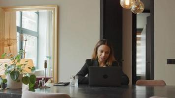 jovem empresária negra sentada à mesa tendo videochamada, falando e movendo as mãos constantemente video