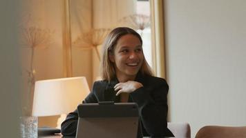jovem empresária negra sentada à mesa, atrás do laptop, conversando video