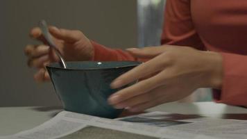 close-up de uma mão feminina negra segurando uma colher, mexendo em uma tigela de sucrilhos video