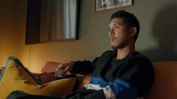 jovem asiático sentado no sofá, tocando no controle remoto, assistindo televisão