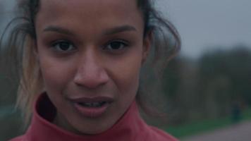 Primer plano de una joven negra, mirando a la cámara, respirando con la boca abierta, gira y se va