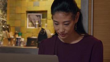 mujer asiática sentada en la cocina, mirando, con los ojos hacia abajo