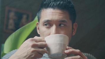 Primer plano de un joven asiático, levantando la taza con ambas manos, tomando un sorbo