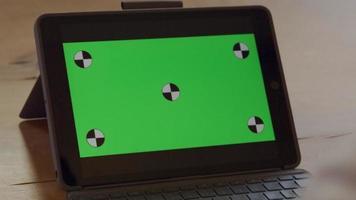 Cerca de la computadora portátil con pantalla verde en la mesa, las manos del hombre maduro en movimiento, gesticulando delante de la pantalla verde video