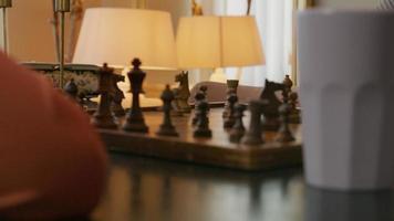 Primer plano de la mano del joven asiático moviendo la pieza de ajedrez, la mano del tablero de puntos de la joven negra