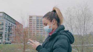 Mujer joven con mascarilla camina afuera, mirando el teléfono móvil mirando hacia arriba y mirando hacia abajo nuevamente