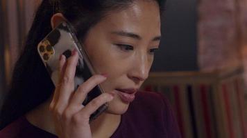 mulher asiática fala com o celular no ouvido, olhos olhando para baixo, acenando levemente com a cabeça, olhos olhando para cima