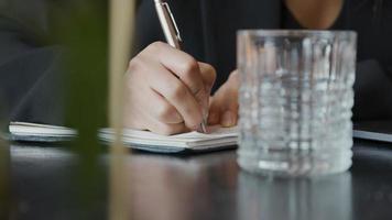La main droite de la jeune femme noire écrit des notes avec un stylo