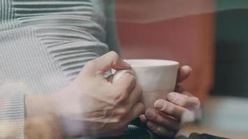 close-up das mãos de um jovem asiático, com as mãos ao redor da xícara, olhando pela janela video