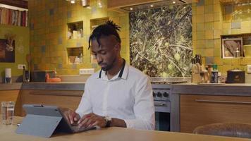 homem negro maduro sentado à mesa da cozinha, os olhos movendo-se ligeiramente para cima e para baixo, a cabeça ligeiramente voltada para baixo, enquanto trabalha no laptop video