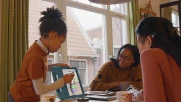 garota em frente à mesa mostra o tablet para duas mulheres, sentadas à mesa video