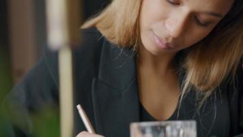 a mão direita de uma jovem negra escreve notas com uma caneta, a mulher olha